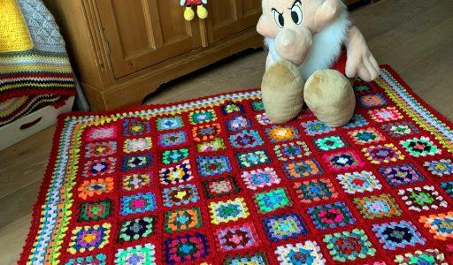 aan de haak met een granny square deken in rood